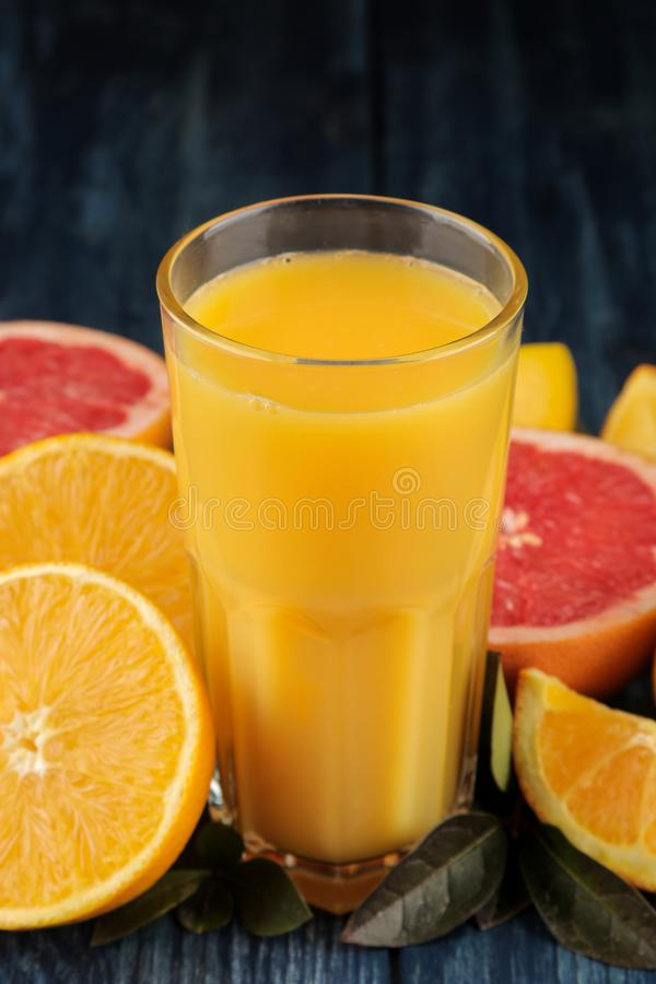 柑橘汁 在玻璃特写镜头的橙汁过去用在一张蓝色木桌上的新鲜水果 库存图片
