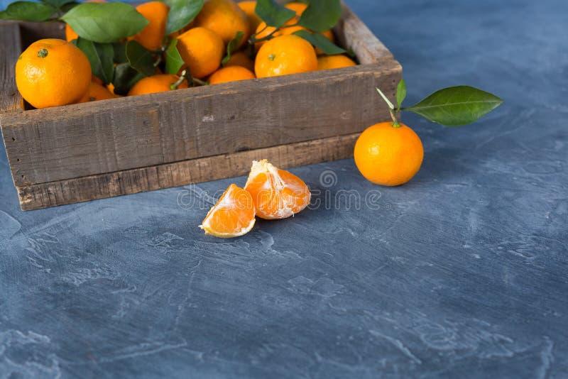 柑橘 与绿色叶子的明亮的成熟蜜桔在木bo 免版税库存照片