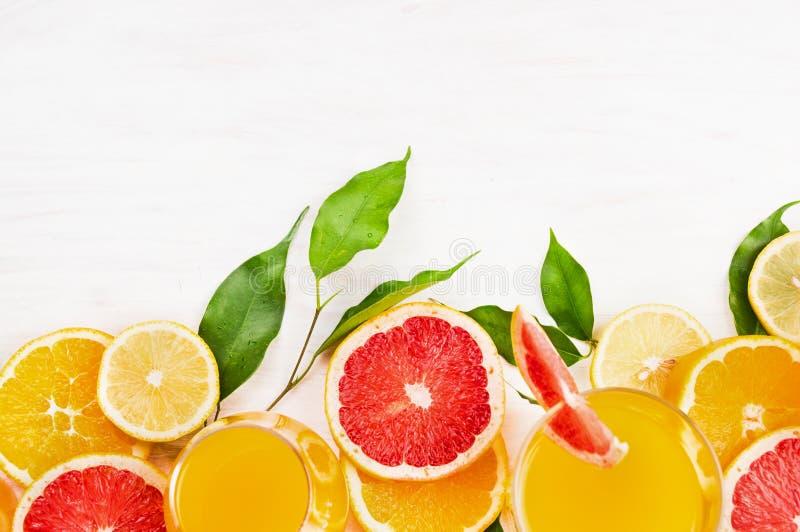 柑橘水果切与在白色木背景的绿色叶子 免版税库存图片