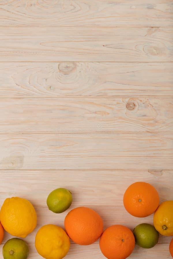 柑橘水果-柠檬、桔子和石灰在轻的木后面 免版税库存图片
