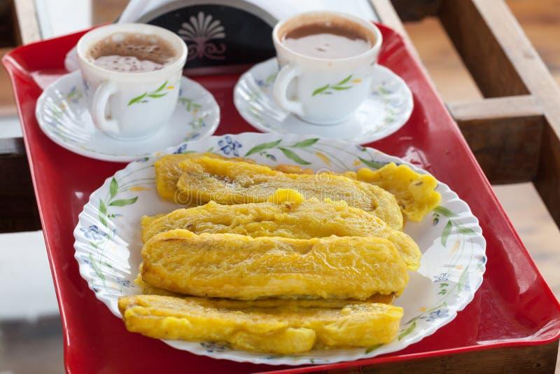 染黄切的大蕉香蕉油炸物,油煎在平底锅用热的椰子 免版税库存照片