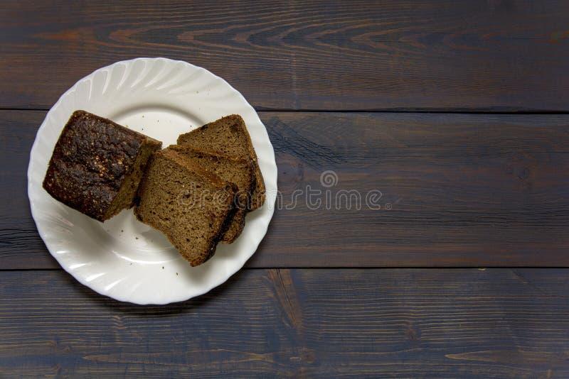 染黑在站立在一张木桌上的一块白色板材的切的†‹â€ ‹面包 库存图片