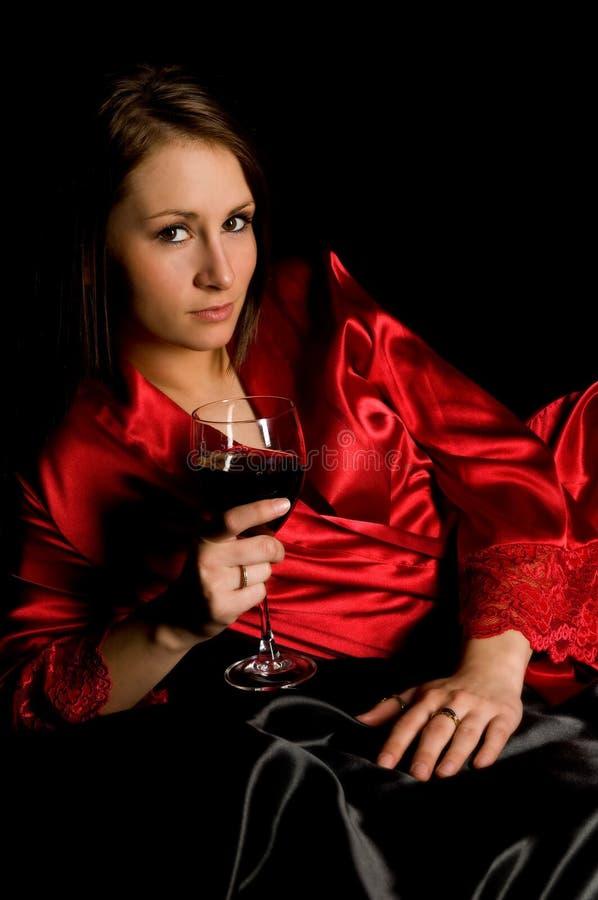 染黑女孩红色长袍缎酒 免版税库存照片