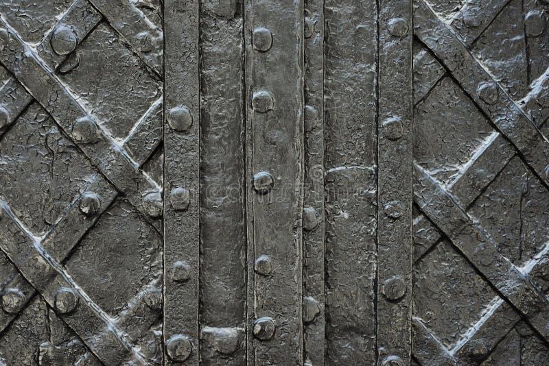 染黑纹理的伪造的铁门或背景,城堡门背景古老建筑学  图库摄影
