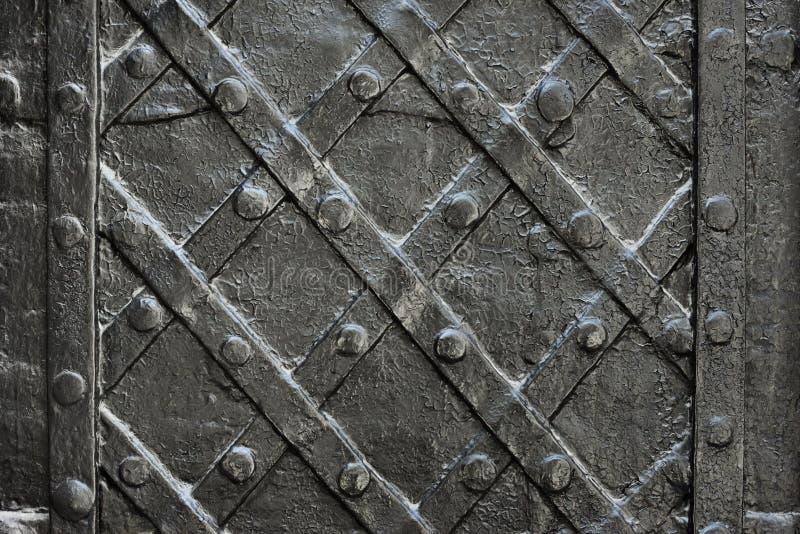 染黑纹理的伪造的铁门或背景,城堡门背景古老建筑学  库存图片