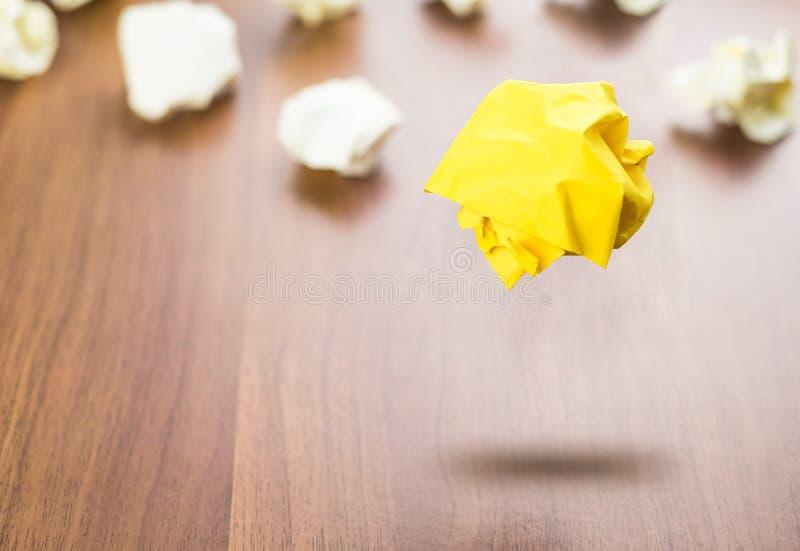 染黄漂浮在w的白皮书球附近的被弄皱的纸球 库存照片