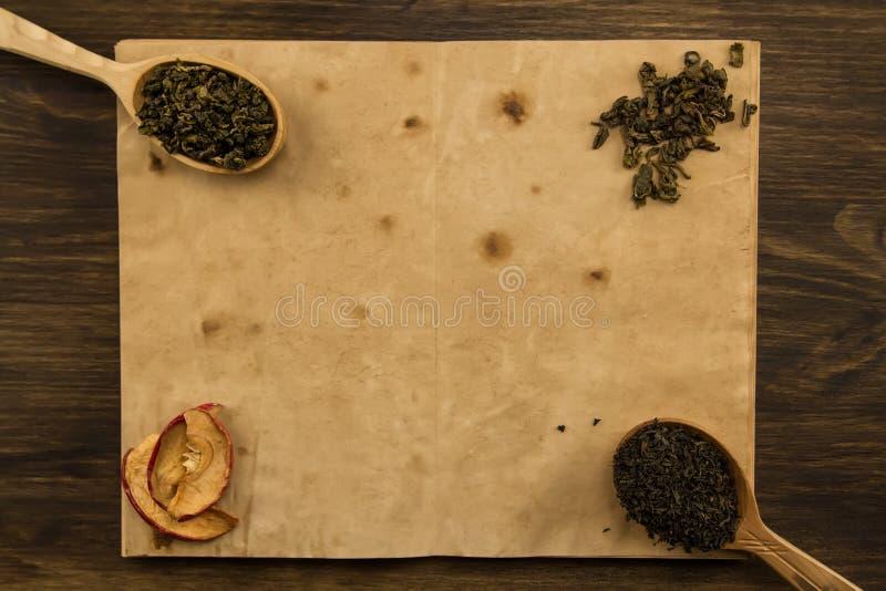 染黑,在匙子的Oolong,在老空白的干苹果打开在木背景的书 免版税图库摄影