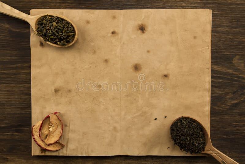 染黑,在匙子的Oolong,在老空白的干苹果打开在木背景的书 免版税库存照片