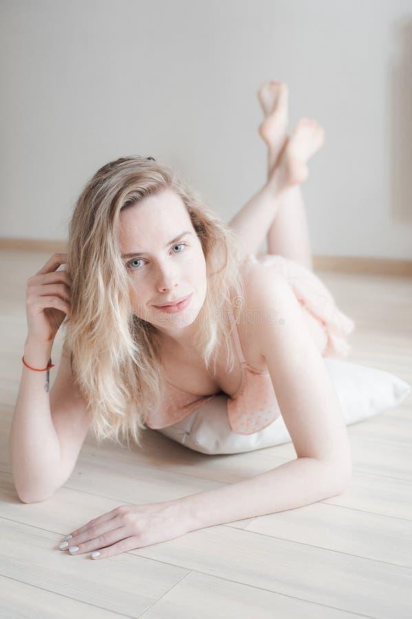 柔和的女用贴身内衣裤的在地板上,看看年轻俏丽的妇女照相机 女性面孔秀丽画象与自然皮肤,没有构成的 免版税库存图片