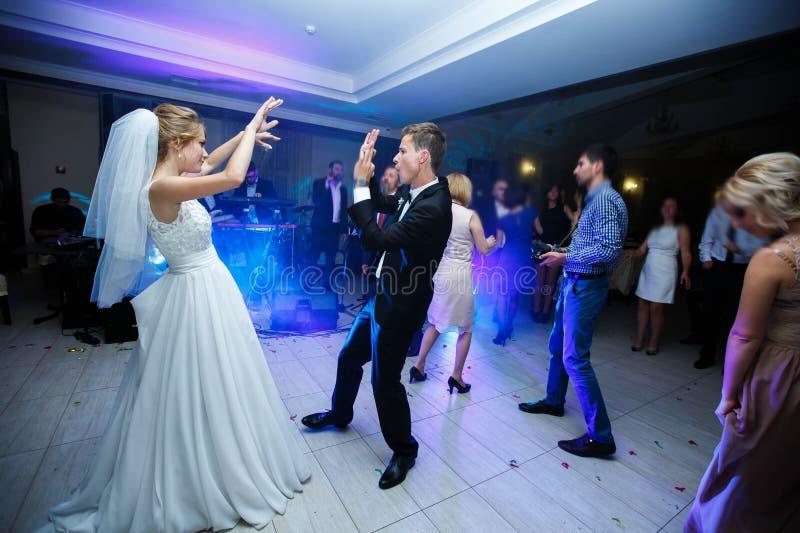 柔和的时髦的愉快的白肤金发的新娘和新郎第一个舞蹈  库存照片