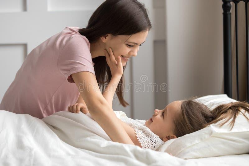 柔和的母亲在下午休息投入女儿睡觉 免版税图库摄影