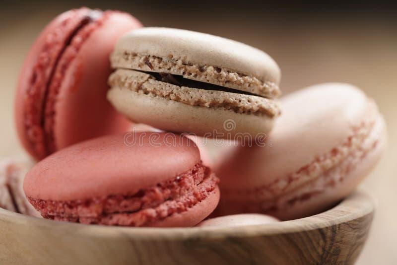 柔和的淡色彩与草莓,玫瑰色和焦糖味道的色的macarons特写镜头射击在木碗 免版税库存照片