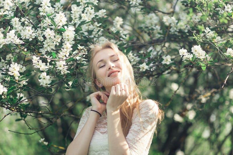 年轻柔和的白肤金发的妇女在开花的庭院里 享受春天的芬芳女孩 她给白色有花边的礼服穿衣 图库摄影