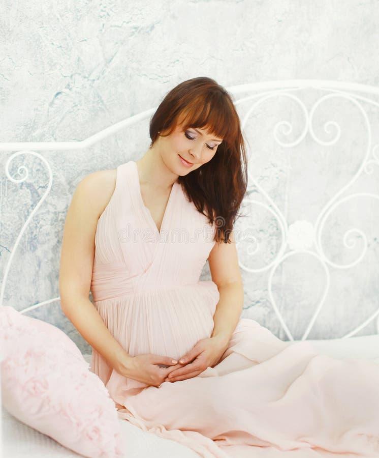 柔和的礼服的美丽的怀孕的少妇在家 免版税库存照片