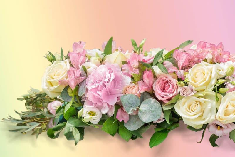 柔和的艺术构成 从分支的花束玉树,八仙花属,德国锥脚形酒杯,在一桃红色梯度backgrou的柔和的玫瑰 免版税库存照片