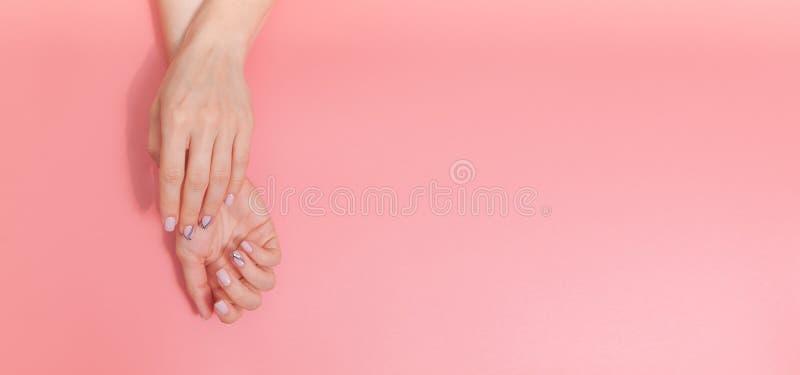 柔和的裸体修指甲 在粉红彩笔背景的女性手与文本的空间 库存照片