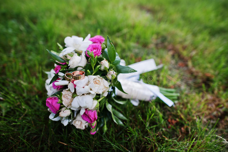柔软与小白色和玫瑰色玫瑰的婚礼花束在gr 免版税库存图片