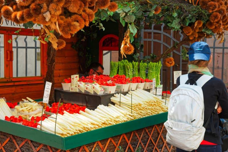 柜台的女孩用新鲜的芦笋和草莓在海得尔堡 库存图片