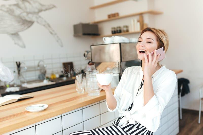柜台的快乐的女孩与咖啡谈话在她的手机在咖啡馆 库存照片
