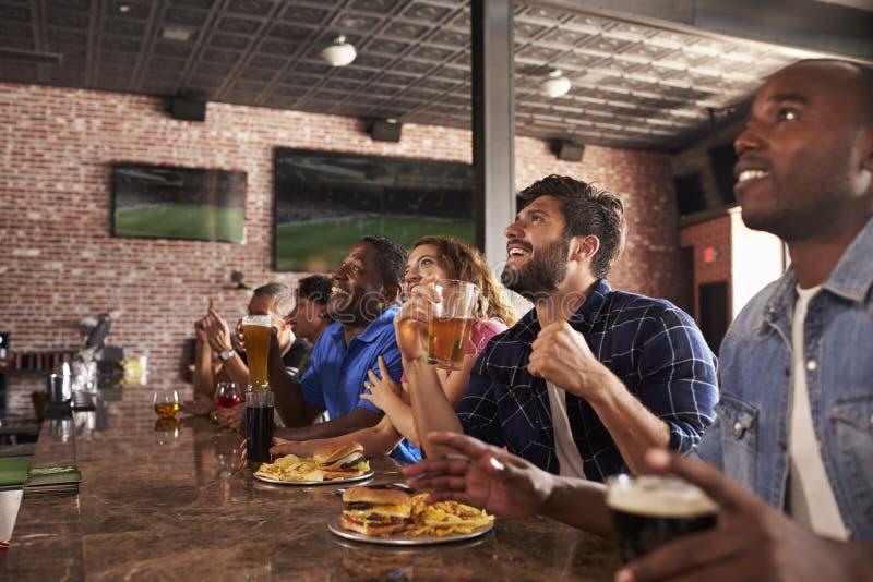 柜台的朋友在娱乐酒吧观看的比赛 库存图片