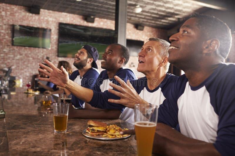 柜台的男性朋友在娱乐酒吧观看的比赛 免版税库存图片