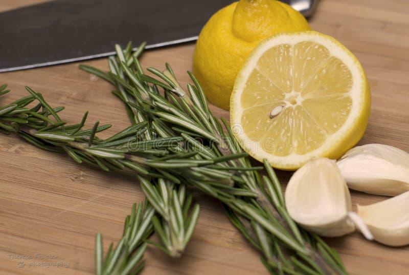 柠檬、罗斯玛丽和大蒜在切板 库存图片