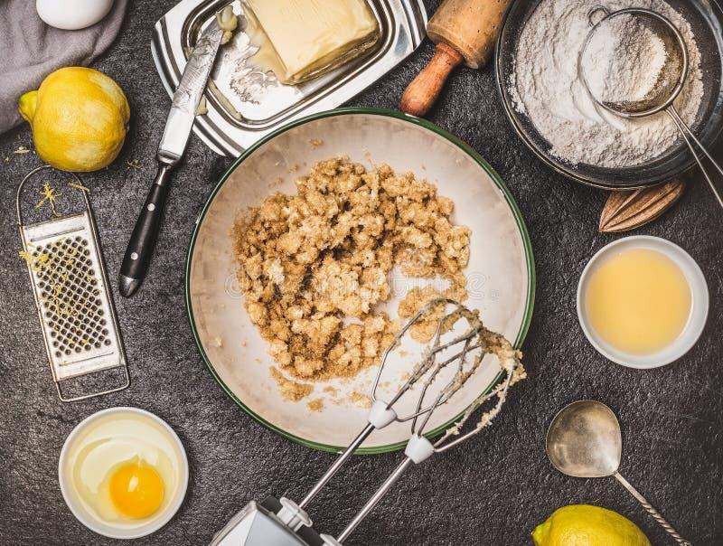 柠檬与烹调成份的曲奇饼或蛋糕准备 混合与在黑暗的厨房用桌backgroun的手搅拌器的黄油和糖 免版税库存图片