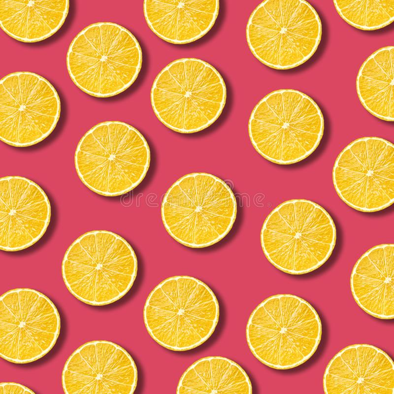 柠檬切在充满活力的石榴颜色背景的样式 免版税图库摄影