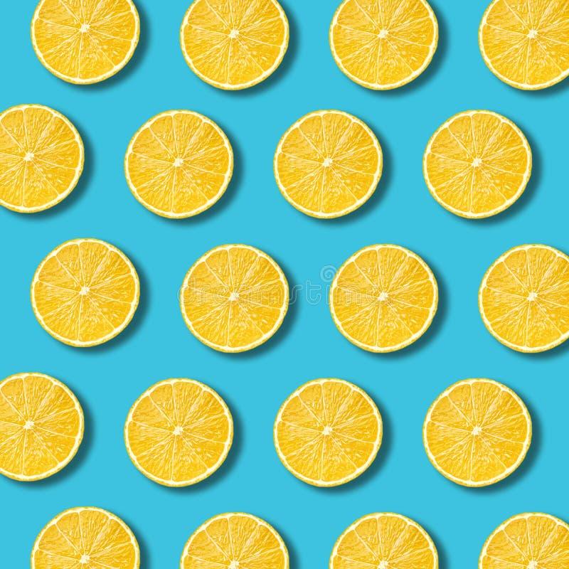 柠檬切在充满活力的绿松石颜色背景的样式 免版税图库摄影