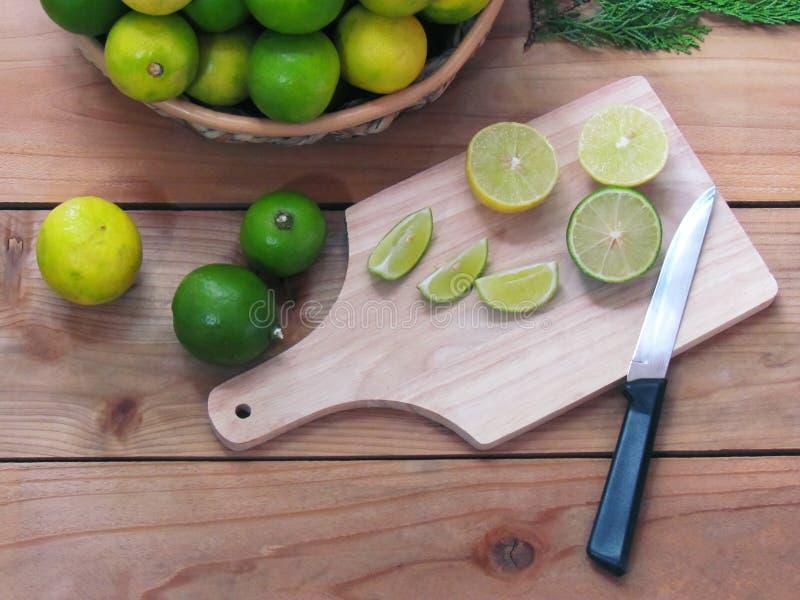 柠檬切片和一把刀子在一块木砧板,新鲜的柠檬 库存照片