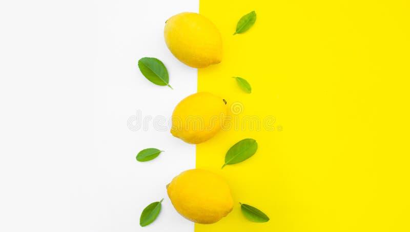 柠檬和叶子顶视图在黄色颜色背景 果子概念想法  免版税库存照片