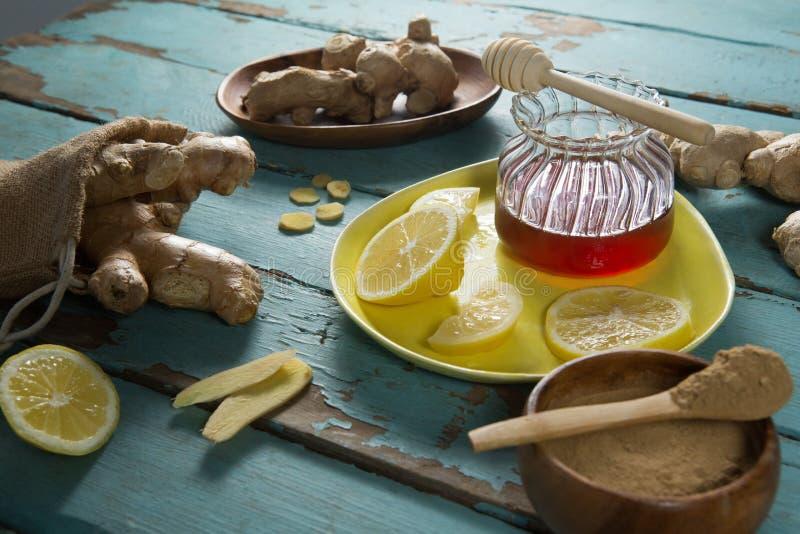 柠檬和姜用蜂蜜在被风化的桌上刺激 免版税库存照片