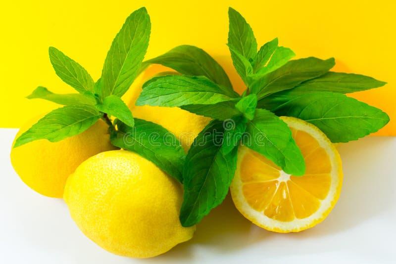 柠檬和新鲜薄荷在明亮的黄色背景 库存照片