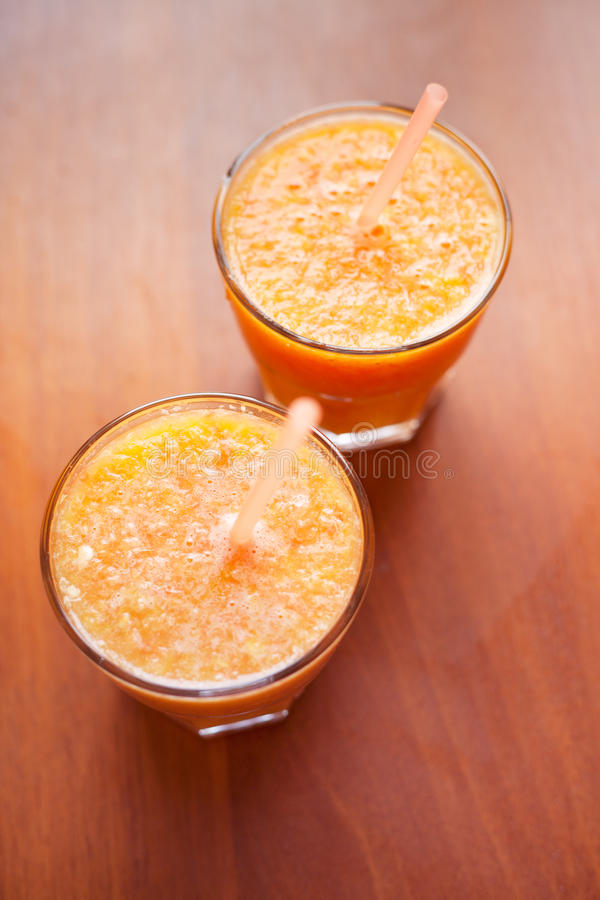 柠檬和橙色圆滑的人在桌上与切片柠檬和桔子在玻璃杯子有管的 库存图片