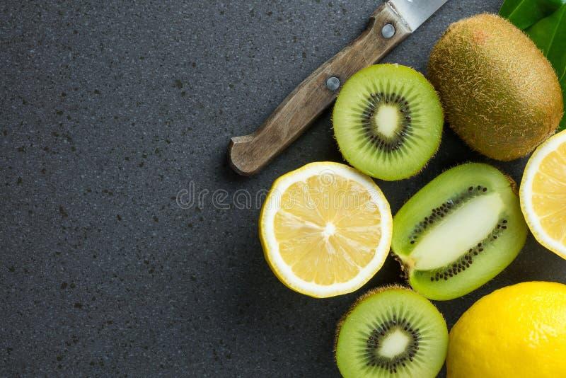 柠檬和猕猴桃是在黑厨房用桌顶部 库存照片
