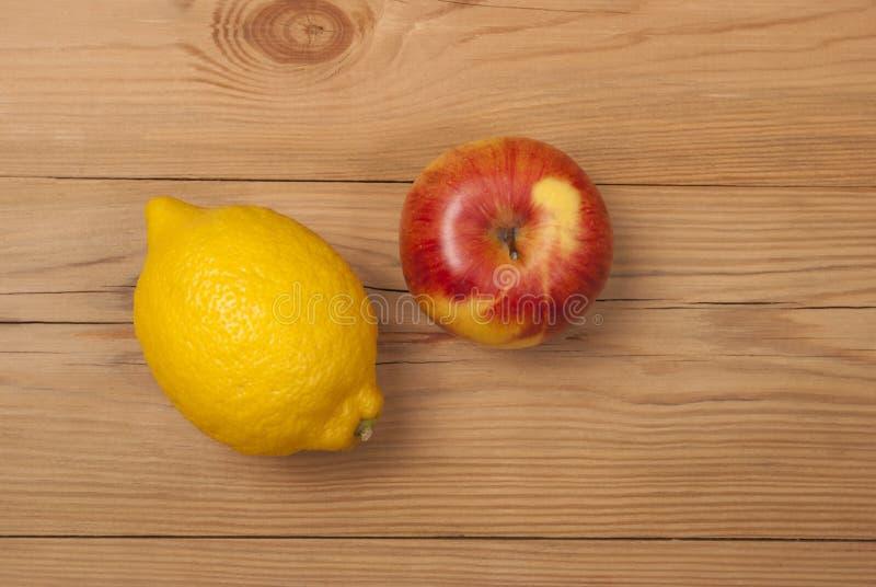 柠檬和苹果在木背景 库存照片