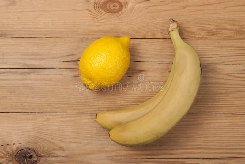 柠檬和香蕉在木背景 免版税图库摄影