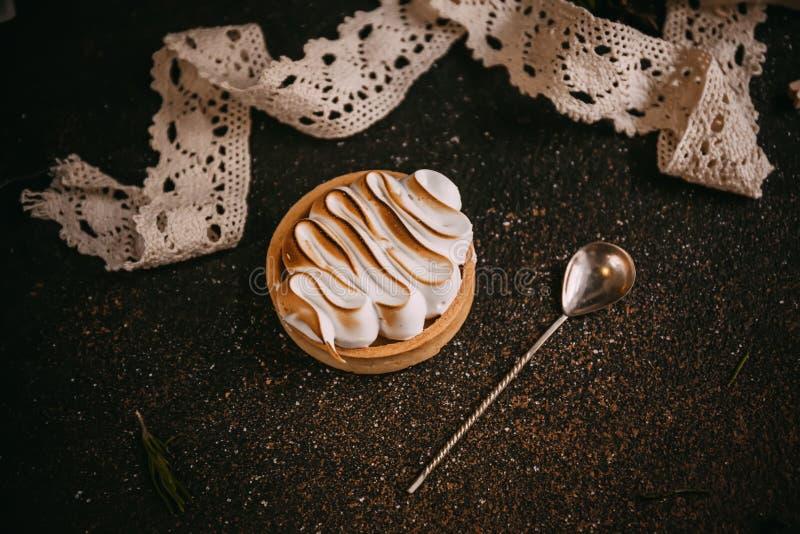 柠檬果子馅饼用蛋白甜饼n石黑暗的桌 库存照片