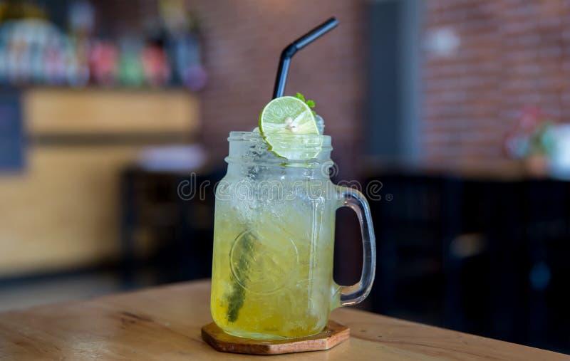 柠檬汁用在木桌上的蜂蜜 在玻璃的柠檬嘶嘶响 免版税库存图片