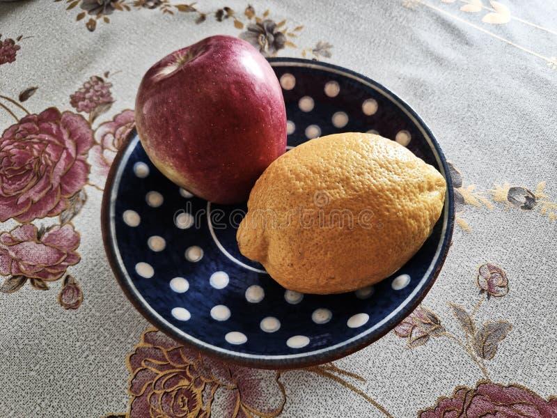 柠檬的摄影图象和在黏土茶碟的一句苹果谎言以与玫瑰的一张桌布为背景与剧烈 库存照片
