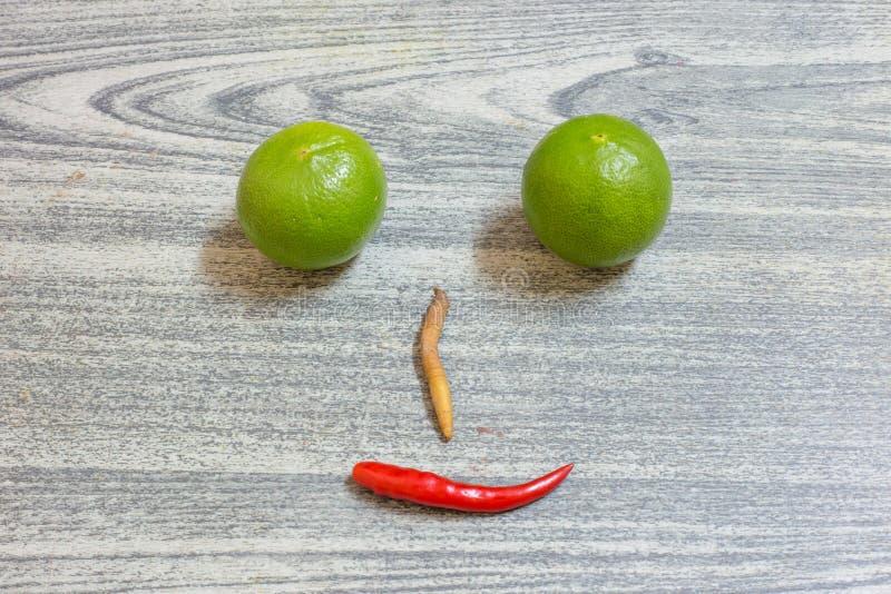 柠檬红辣椒fingerroot是在木背景的面孔 免版税库存图片