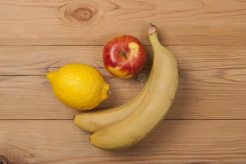 柠檬苹果和香蕉在木背景 库存照片