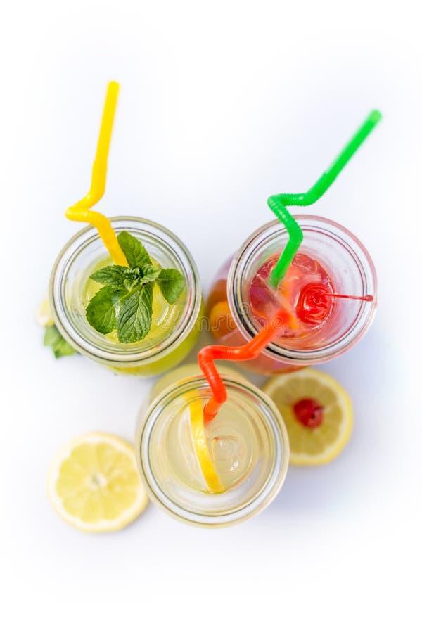 柠檬水不同的技巧在水罐的有秸杆和柠檬的在白色背景 免版税库存照片