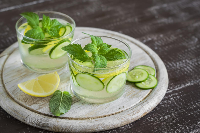 柠檬水用黄瓜、柠檬、薄菏和姜在玻璃杯子 免版税库存照片