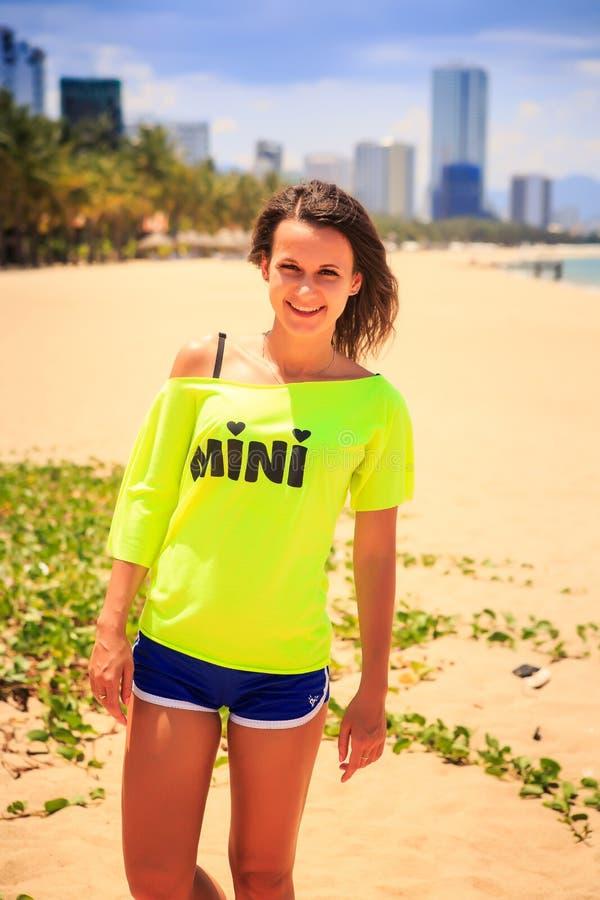 Download 柠檬T恤杉的亭亭玉立的女孩在海滩微笑反对游览城市 库存照片. 图片 包括有 室外, 蓝色, 掌上型计算机 - 59105104