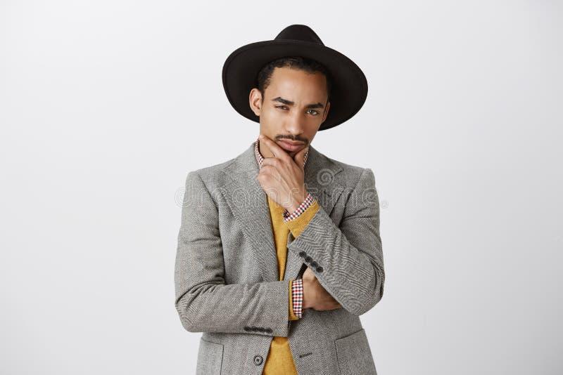 查出在您的眼睛在 可疑被聚焦的年轻深色皮肤的男性设计师演播室射击时髦的衣裳的和 免版税库存照片