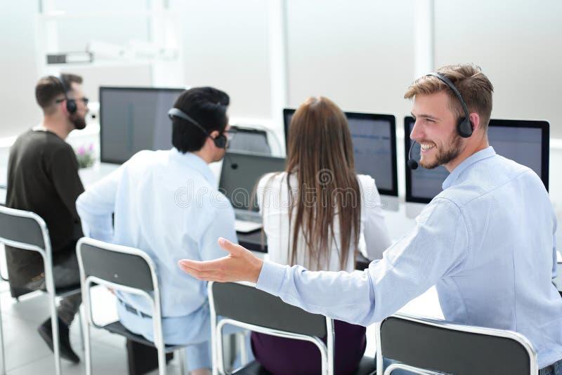 查出的背面图白色 小家伙坐在他的书桌的服务代理 免版税库存图片
