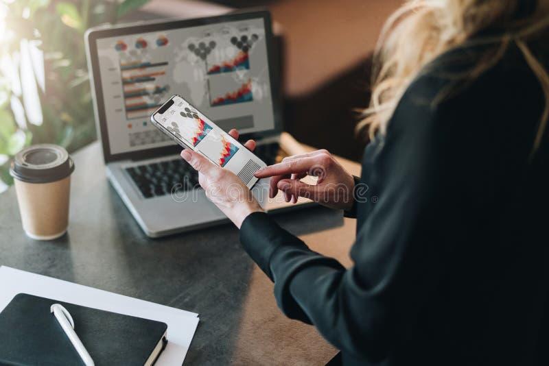 查出的背面图白色 工作在有图表的,图,在屏幕上的图智能手机的年轻女实业家 网上营销,教育 免版税图库摄影