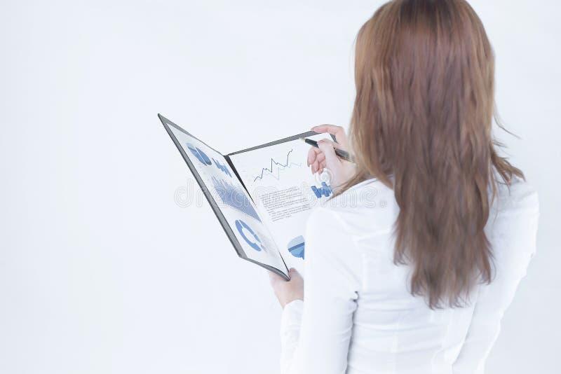 查出的背面图白色 检查财政报告的女商人 免版税库存照片