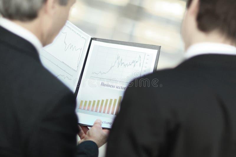查出的背面图白色 的商务伙伴特写镜头谈论财政文件 免版税库存图片